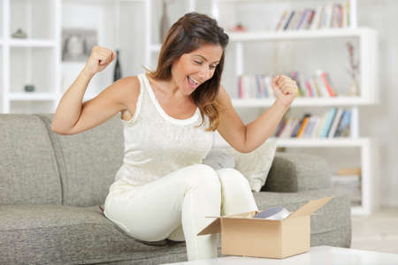 happy woman with product parcel box at home