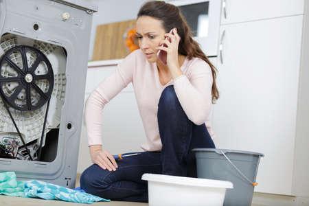 upset woman claiming insurance for washing machine leaks Stock Photo