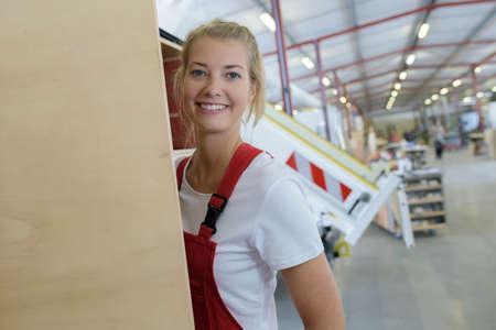 donna felice che lavora in una fabbrica di legno