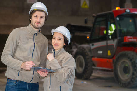 two workers with clipboard in dark warehouse