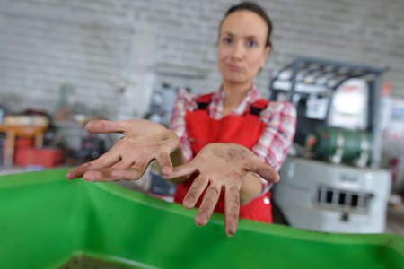 female worker ruefully showing her dirty hands