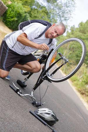 volwassen man die zijn fiets in het bos repareert