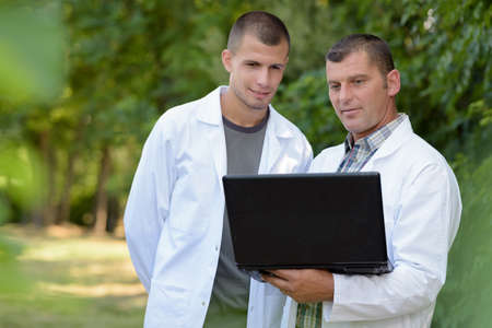 man and apprentice in white coat using laptop Zdjęcie Seryjne