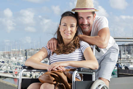 happy couple in wheelchair posing in a port