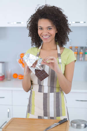 smiling woman holding bar of chocolate Stock Photo