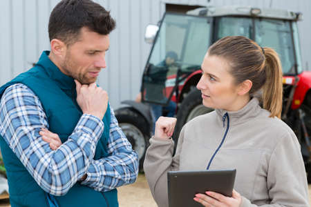male and female farmers talking next to a tractor