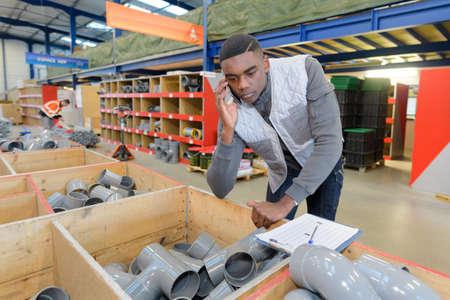 Employé d'entrepôt transportant un tuyau dans un entrepôt