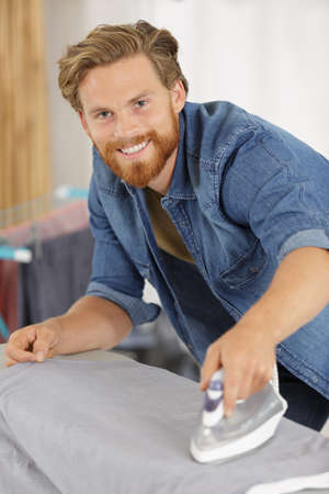 handsome happy man ironing clothes Stock Photo
