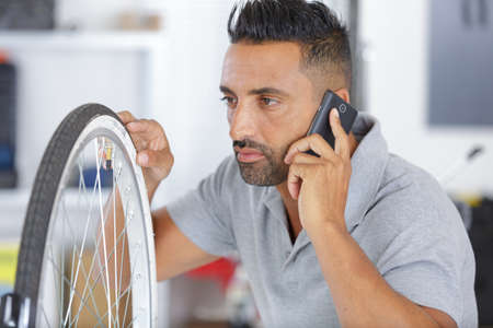 man calling someone about repairing bicycle at home 스톡 콘텐츠