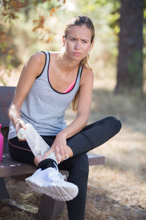 fitness woman suffering painful ankle sprain injury after running Stock Photo