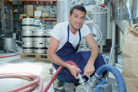 male brewery worker with bottling machinery on factory