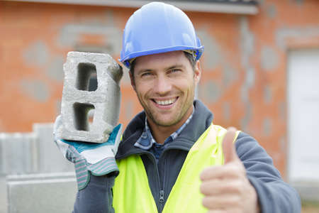 smiling builder worker at construction site showing a thumb up