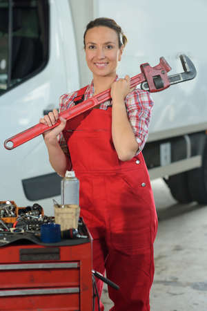 woman holding big wrench