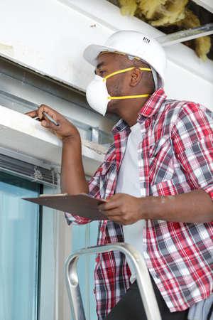 inspector wearing dust mask examining building