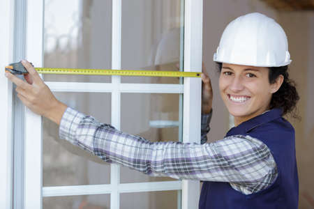 young happy woman measuring window