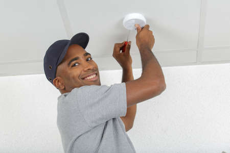 electrician removing battery from smoke detector Stock fotó