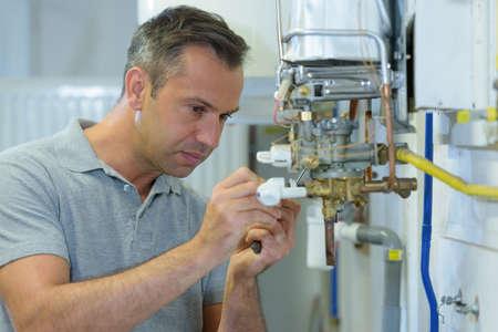 männlicher Ingenieur, der einen Gaskessel repariert