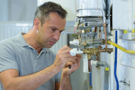 mannelijke ingenieur die een gasboiler repareert
