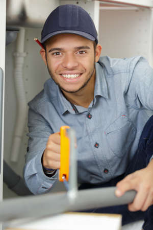 happy young man saws pipe wrap Stock Photo