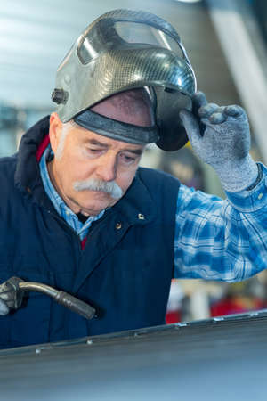 senior man wearing visor to use blow torch
