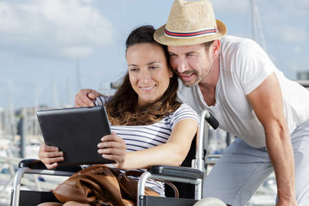 couple by harbour looking at tablet woman in wheelchair