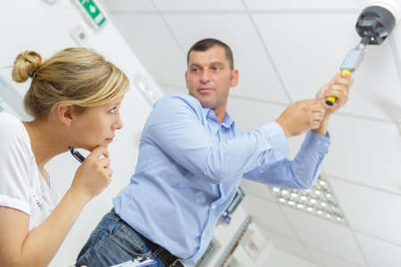 man testing a ceiling mounted detector
