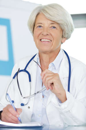 senior female doctor sitting at desk in an office portrait