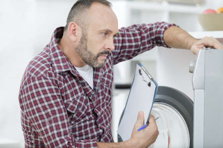 mature serviceman with clipboard looking at washing machine