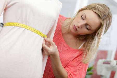young tailor measuring the mannequin waistline Stock Photo