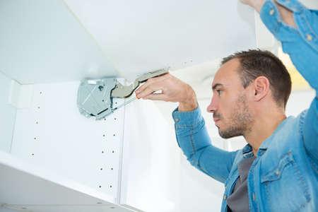 man fixing hanging cabinet door mechanism 版權商用圖片