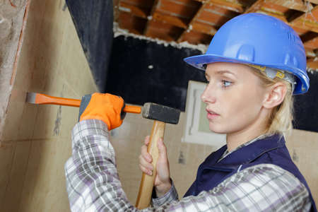 female builder with hammer and chisel