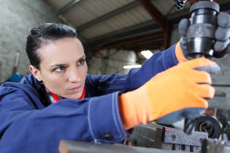 female apprentice using drill in factory Imagens