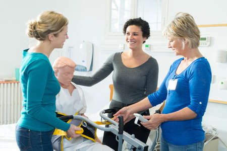 nurses practicing procedure to lift disabled patient from bed