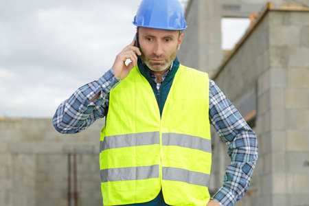 male builder foreman architect on building site using phone