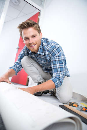 worker rolling carpet at home