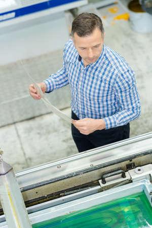 man holding sheet looking at liquid factor