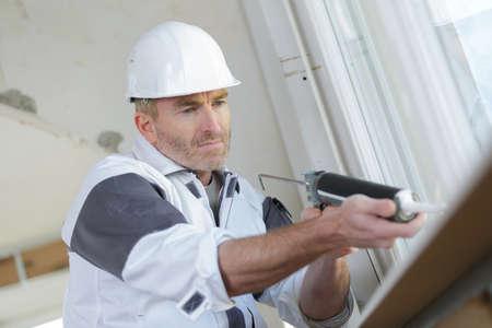Worker using caulking gun