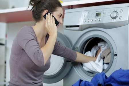 Mujer vistiendo camisa blanca con teléfono inteligente cerca de la lavadora