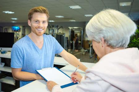 ältere Frau, die sich im Fitnesscenter anmeldet