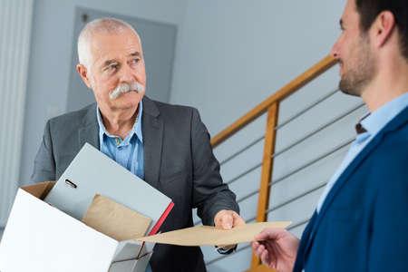 elderly employee leaving office with box full of belongings Stock Photo