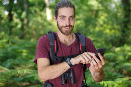 man with phone in forest