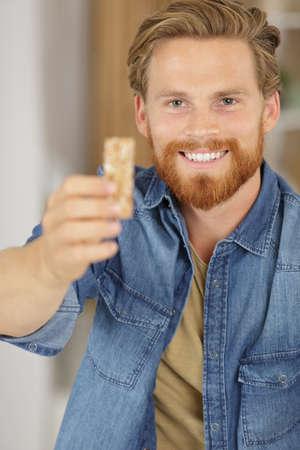 man eats a cereal bar Stock fotó