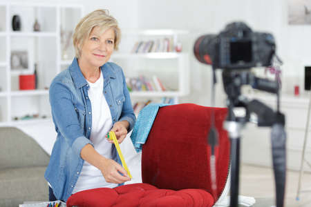 woman filming herself measuring chair for her blog