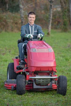 Joven jardinero en un tractor cortacésped