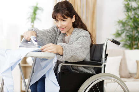 disabled woman ironing at home and smiling