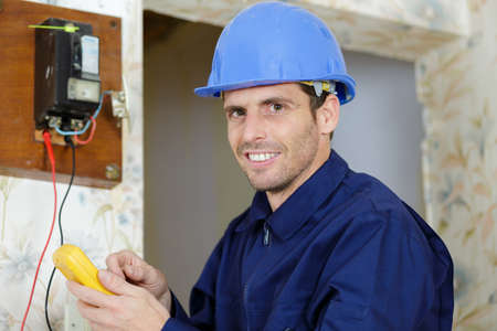 technical electrician measures the voltage of a circuit breaker