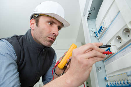 electrician testing power from electrical panel