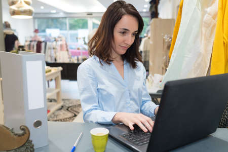 clothing boutique manager using a laptop