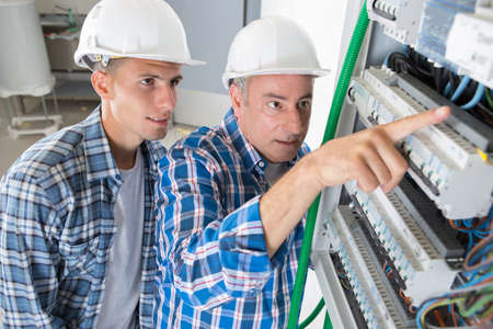journeyman and apprentice electrician working to repair a circuit panel Stok Fotoğraf