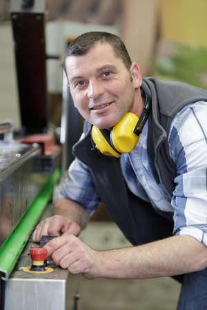 a male factory worker smiling at the camera